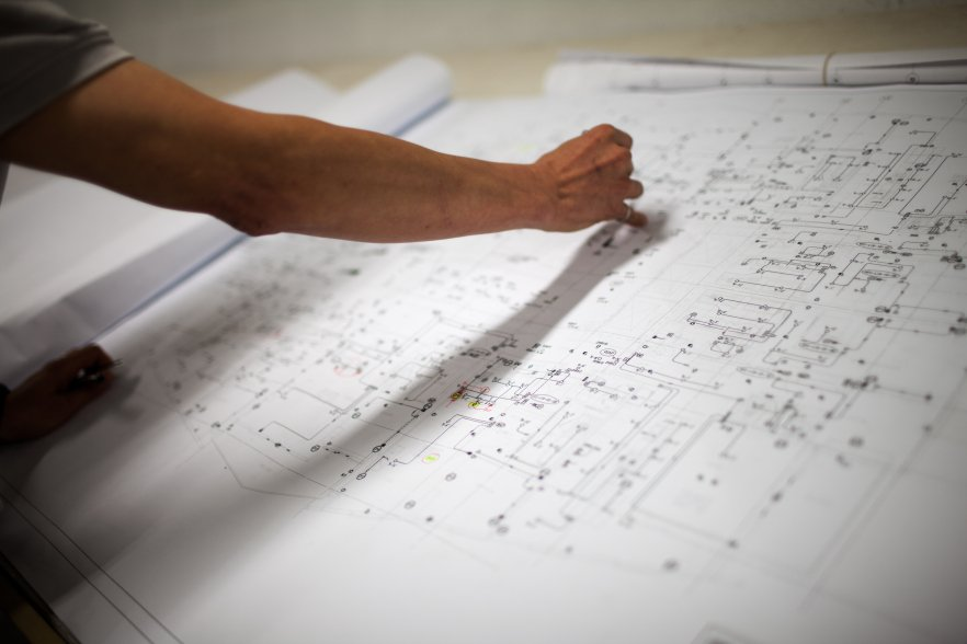cropped image of a engineer working on blueprint